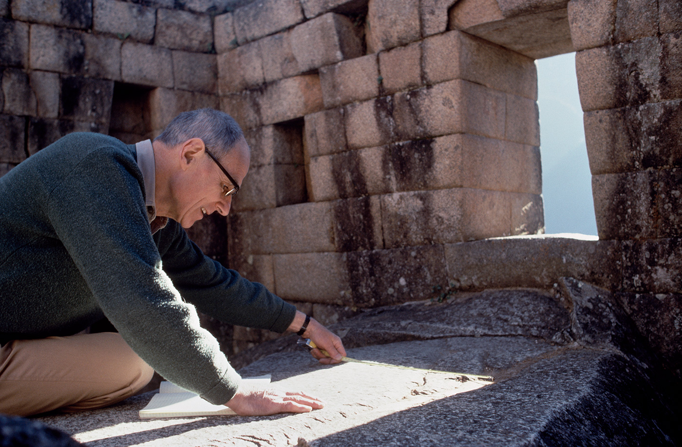 John Rowe, archaeologist, measures the sun's alignment through a temple window during the June solstice at Machu Picchu.