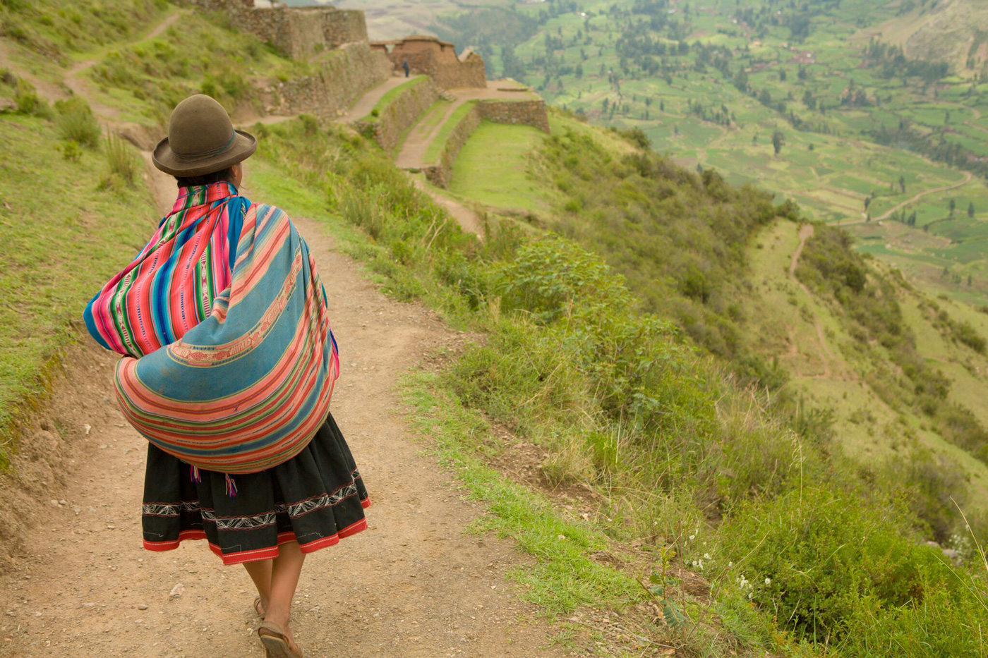 A Peruvian woman selling textiles in Pisac National Park walks past terraced fields in the distance.