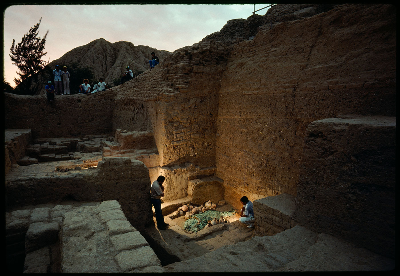 Archaeologists Walter Alva (left) and Luis Chero gaze into the recently excavated tomb. Ceramic jars surrounding the warrior-priest's remains may have held offerings.