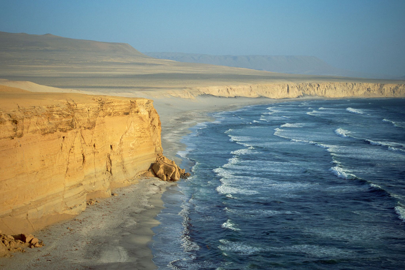 Dry, weather-beaten sea cliffs rise from the Pacific Ocean in the vicinity of the Paracas Peninsula.