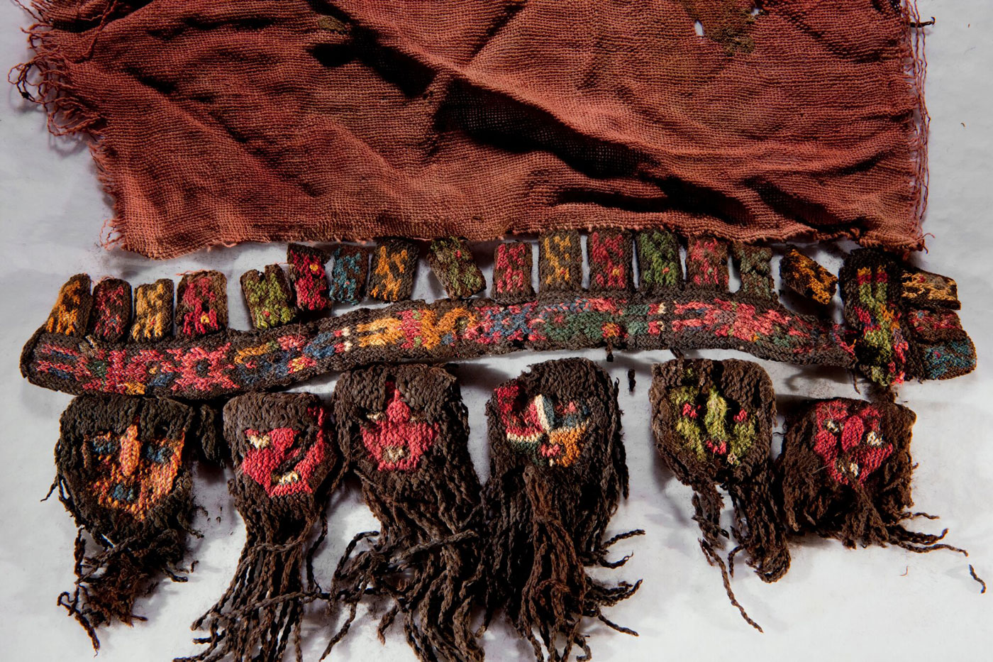 The sacred symbols of the Nasca reverberate through their material culture. Adorning the border of a ceremonial shawl from Cahuachi, long-haired heads mimic real sacrificial heads.