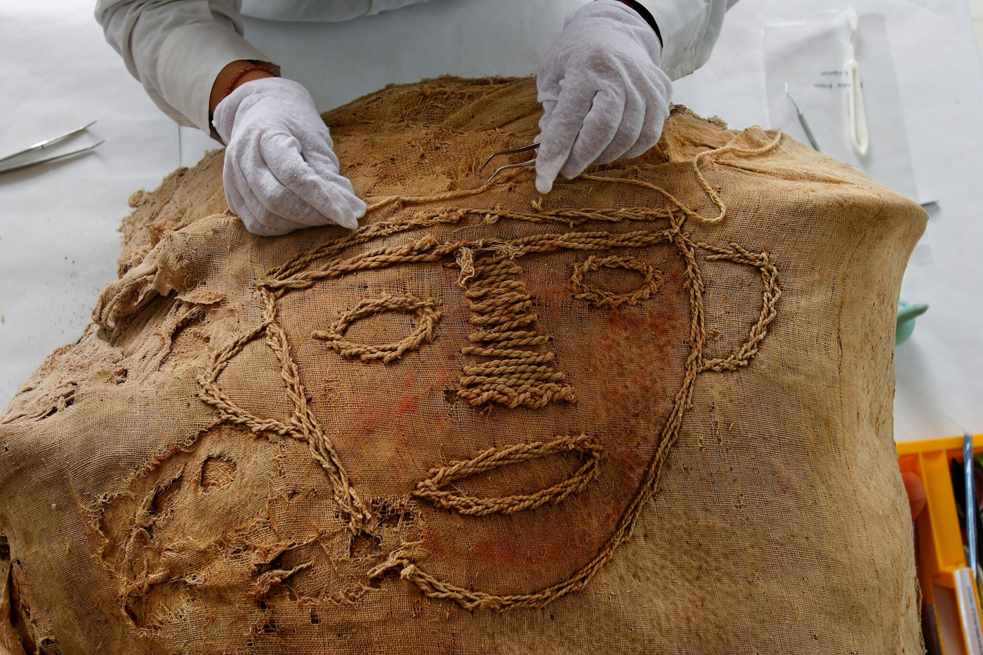 """The mummy bundle of the woman discovered at El Brujo included a surprising detail not typically found in Moche burials. Adorning her funerary bundle was an embroidered face (pictured). To start the delicate process of unwrapping the mummy for study, textile expert Arabel Fernández López carefully removed the stitches. """"I think the face humanized the bundle and reminded mourners that this was no ordinary person,"""" Fernandez says."""