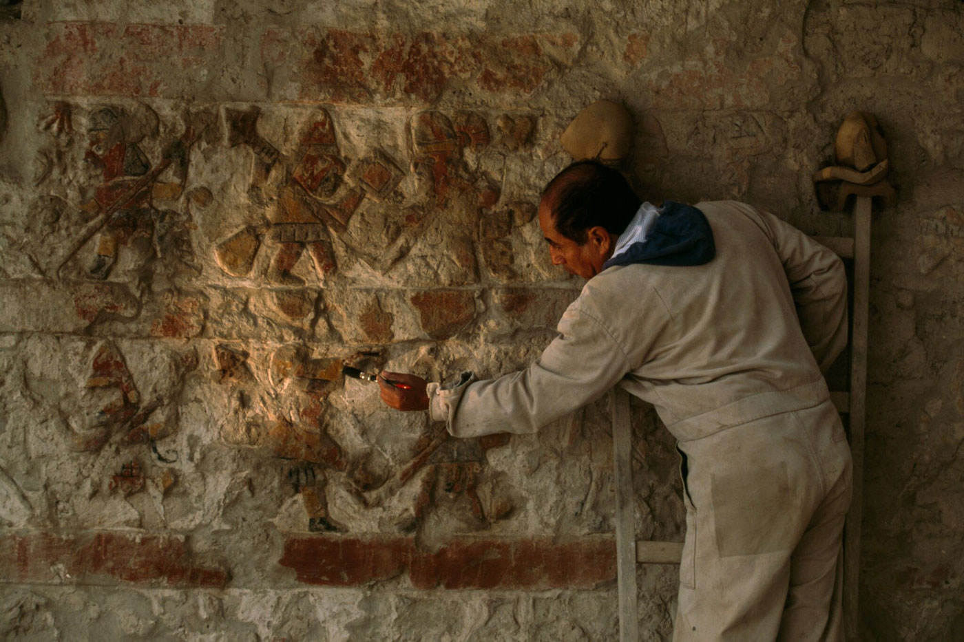 A conservator cleans a 1,600-year-old relief depicting Moche warriors.