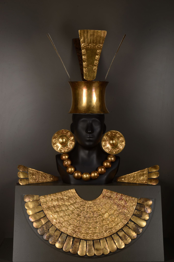 This is a headdress with a solid gold pectoral, or breastplate, crafted by the Chimú. It was most likely worn by a person of elite status buried at Chan Chan, the Chimú capital. The ear spools feature a Chimú deity, and the gold plates on the crown symbolize birds and the sun. The epaulettes, or shoulder pieces, show the Chimú lord holding trophy heads.